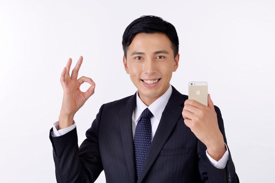 右手でOKサインかお金を表す指サインでアイフォンを片手に作り笑顔のイケメン