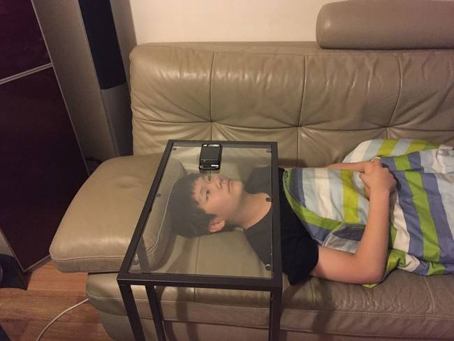 ガラステーブルでスマホを見る怠け者の画像