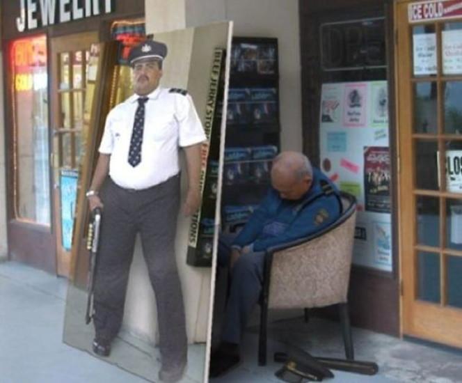 看板の裏で眠る警官の画像