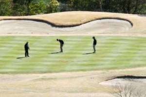 ゴルフのグリーンに立つ3人