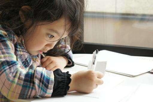 暗い部屋で勉強する子供