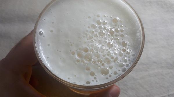 第三のビールを入れたグラスを持っている。