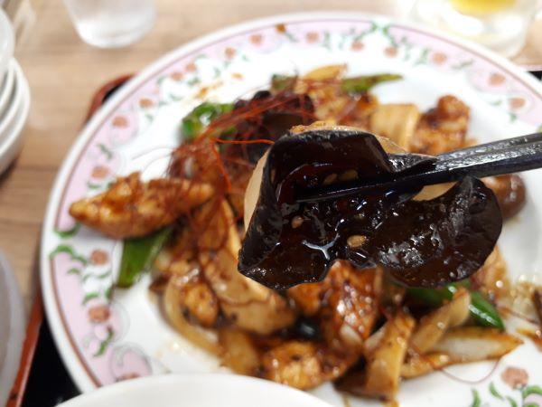 鶏ときのこの旨辛豆豉炒めを食べている