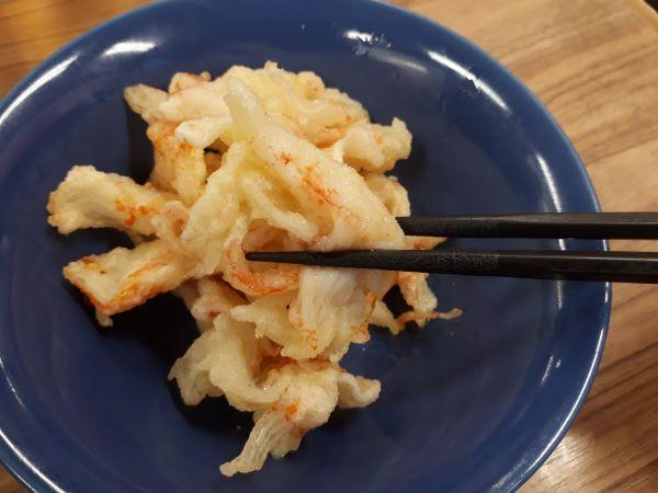 餃子の王将のカニカマの天ぷらを食べているところ