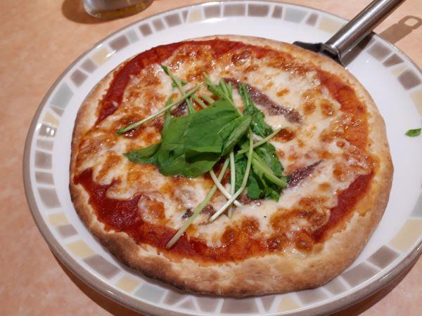 サイゼリヤのアンチョビのピザを食べるところ