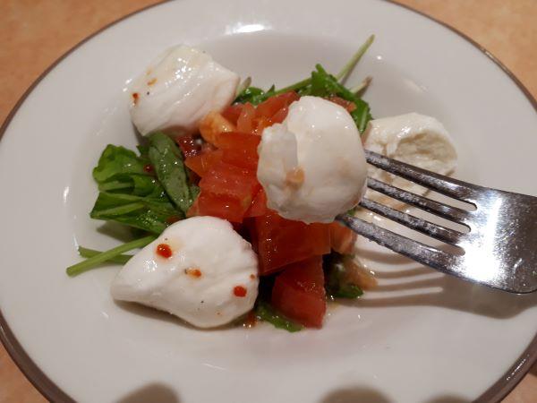 サイゼリヤ「フレッシュチーズとトマトのサラダ」を食べるところ