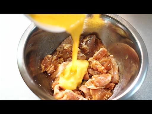 鶏もも肉へ溶き卵をかける