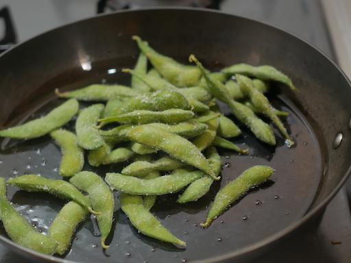 フライパンへ枝豆を入れる