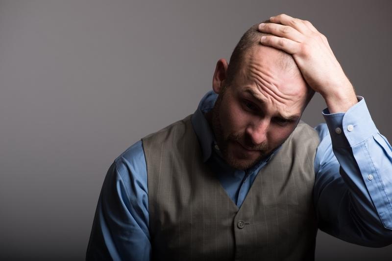 頭を抱える外国人男性