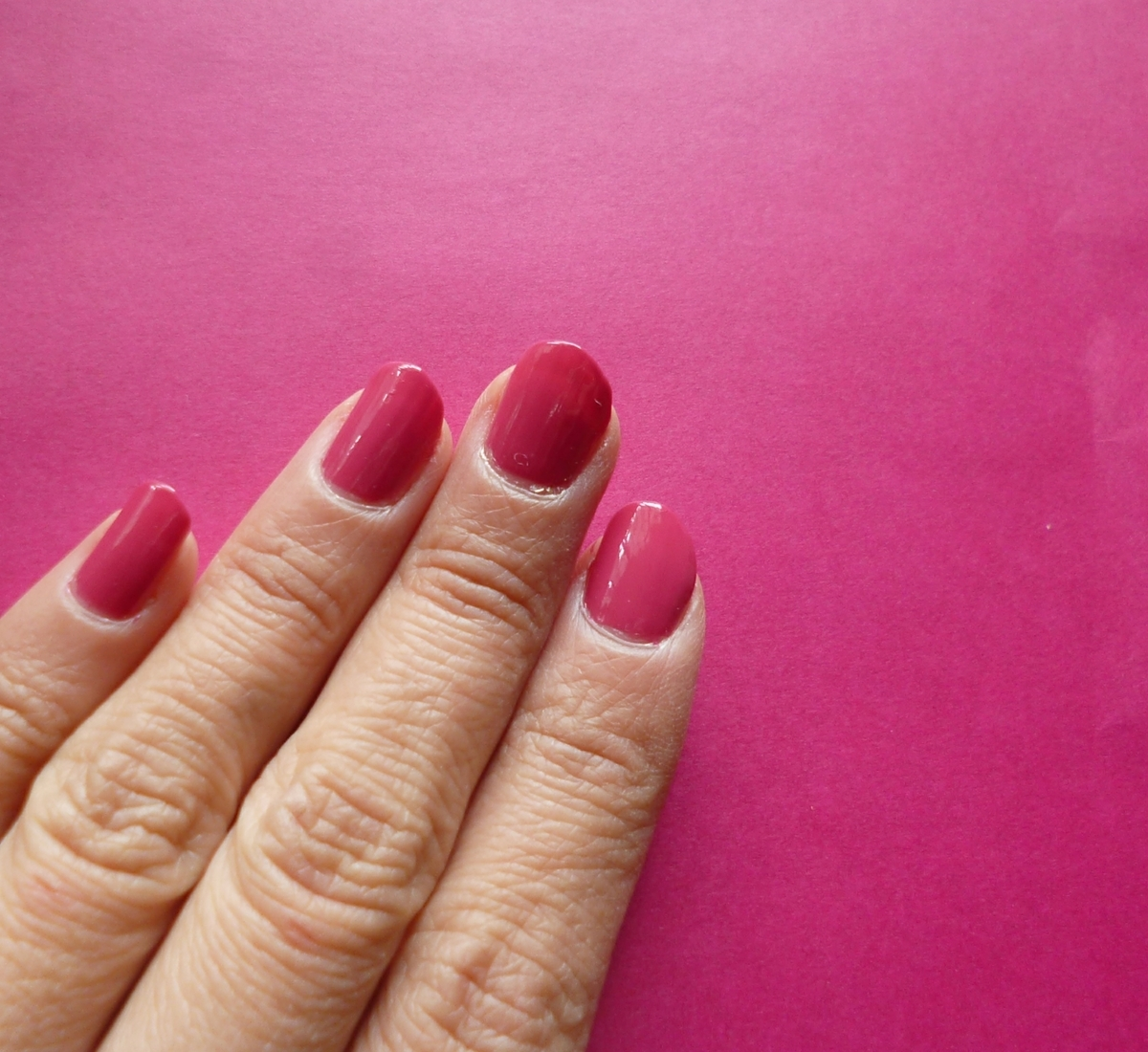 赤紫色の折り紙とマニキュアを塗った爪の色比較