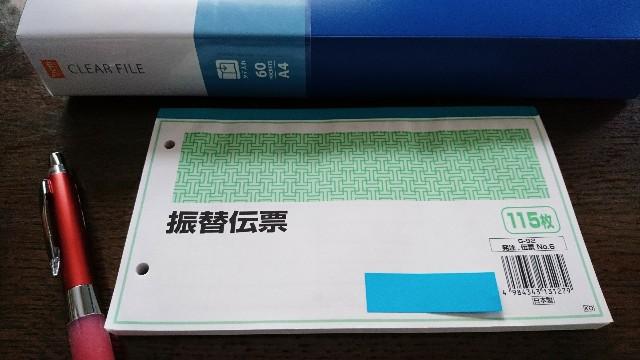 振替伝票とシャーペンと青いファイル