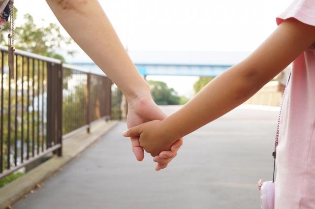 こどもと手を繋いで歩く写真