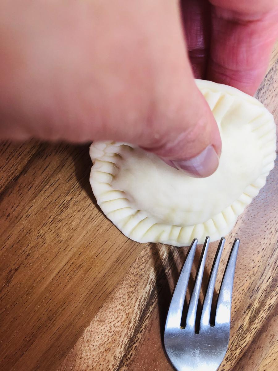 《皮に具を包む》具を置き、周りに水を指でくる〜と回し付け、もう一枚を重ねてフォークで押さえる。