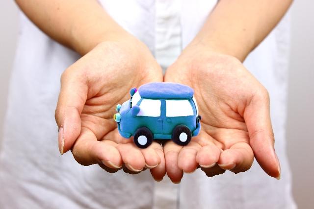 手のひらに載っている車のおもちゃ