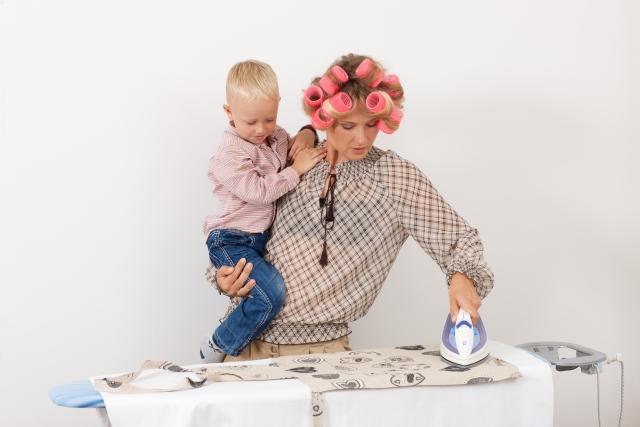 子どもを抱っこして家事する母親