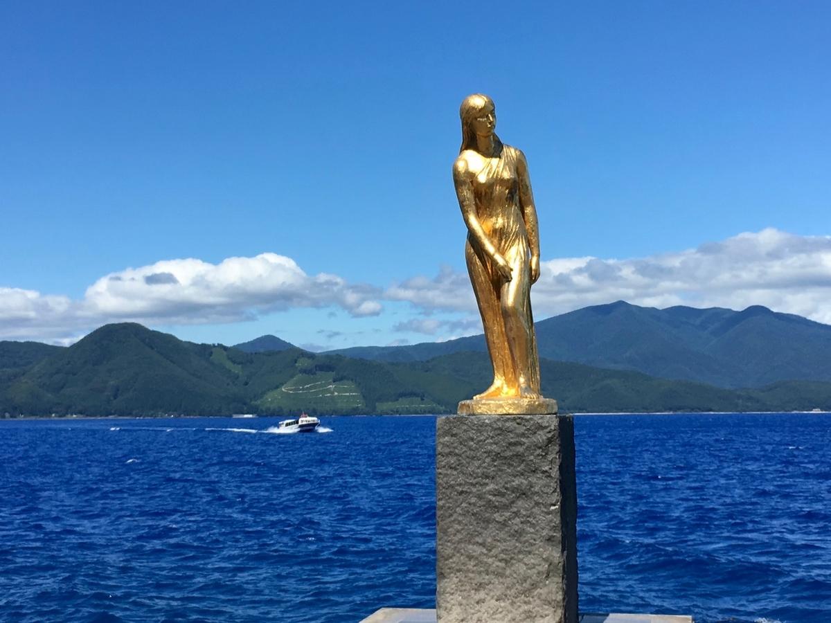 田沢湖ブルーにじっとたたずむたつこ像