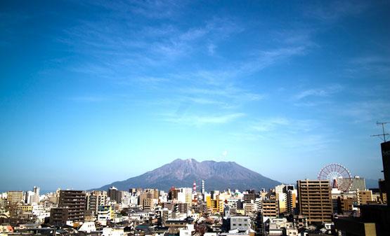 高台から望む桜島の写真です。右の方に見えているのはアミュランという観覧車で鹿児島のランドマークです