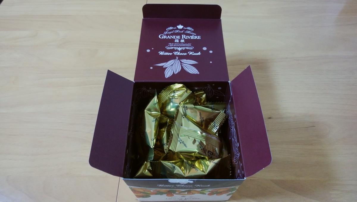 「箱根ビターショコラスク」の箱を開くと金色の個包装が見えている。