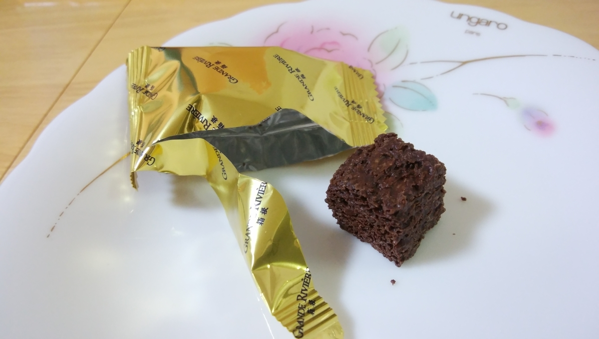 金色の個包装から出てきた「箱根ビターショコラスク」が皿の上にある。