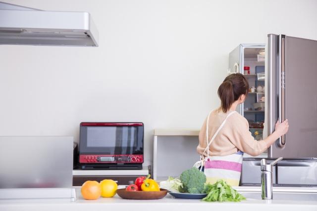 キッチンで冷蔵庫を開ける女性の後ろ姿