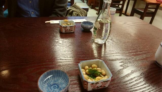 テーブルの上の、ぬる燗した日本酒と豆のお通し
