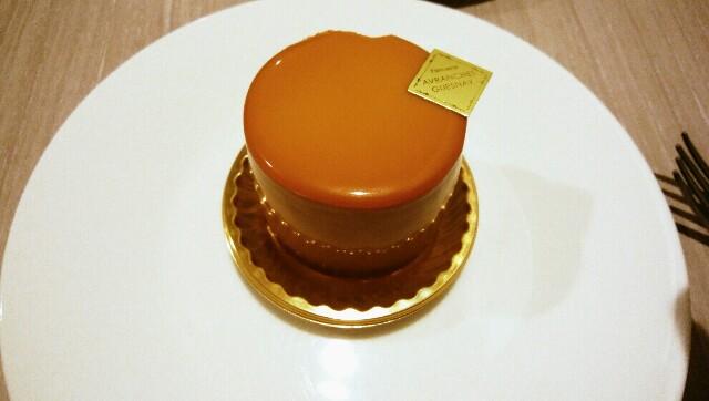 キャラメル色で円柱形をしている、つるんとした表面のケーキ