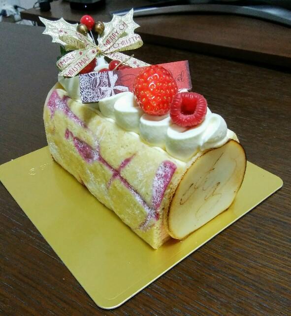 ロールケーキ状で、クリームや苺でデコレーションされているケーキ