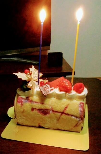 ケーキにロウソクが2本立てられ、火がともっている。