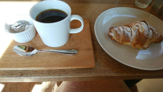 アーモンドスライスとパウダーシュガーがかかったクロワッサンと、コーヒーのアップ