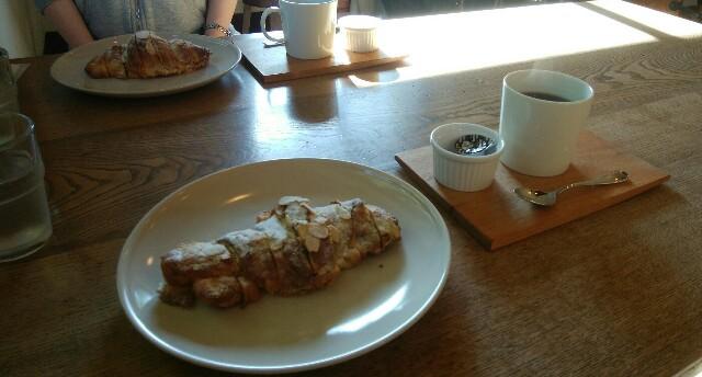 大きな木のテーブルに「アーモンドクロワッサン」とコーヒーが2セットある。