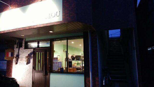 暗闇に明るい店内が見える「パティスリー・ムゥ」の店舗入口
