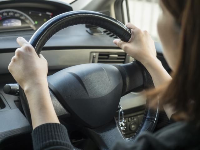 運転席でハンドルを握る女性