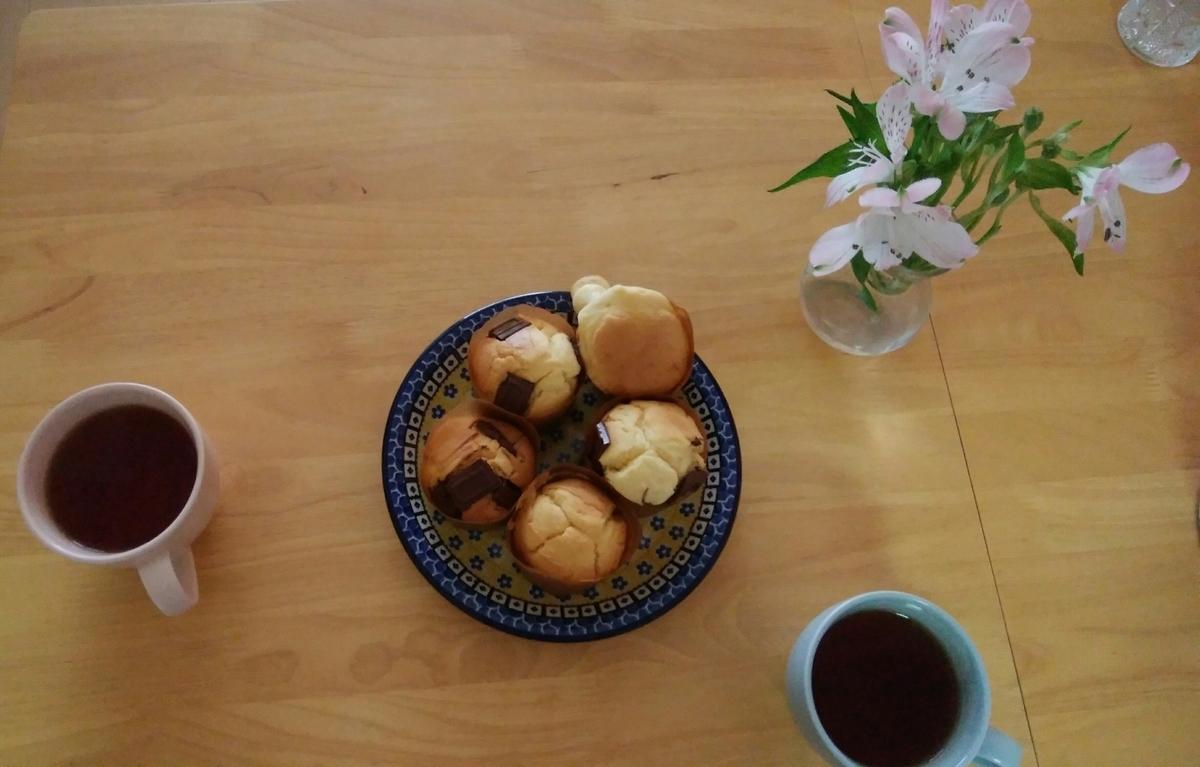 テーブルの上にマフィンをのせた皿と紅茶が入ったマグカップと花瓶がある。