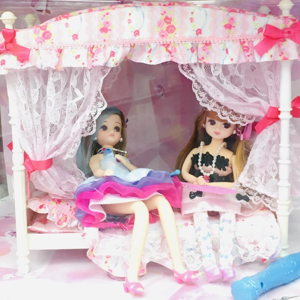 ヨドバシカメラの「リカちゃん」売り場にディスプレイされた天蓋付きベッドに腰掛けるリカちゃんの友人ふたり
