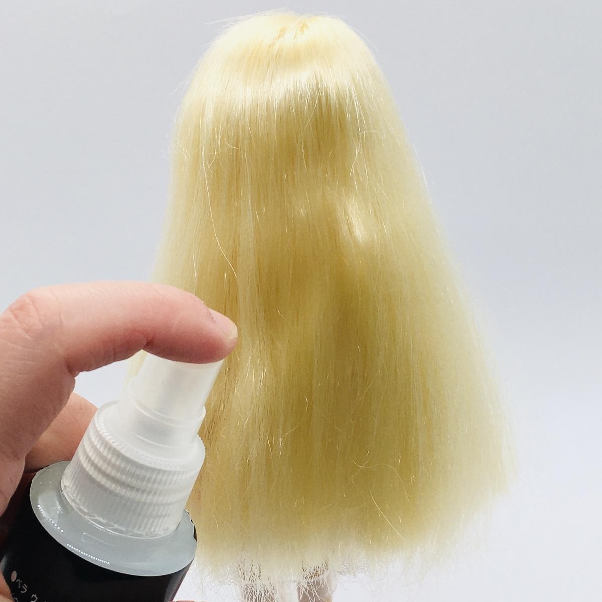 「みさきちゃん」の髪の毛にウィッグオイルをスプレーしているところ