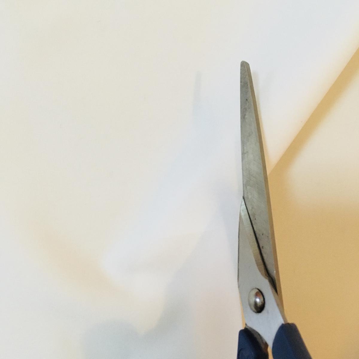 ハサミでダイソーの白いハギレを切っていく