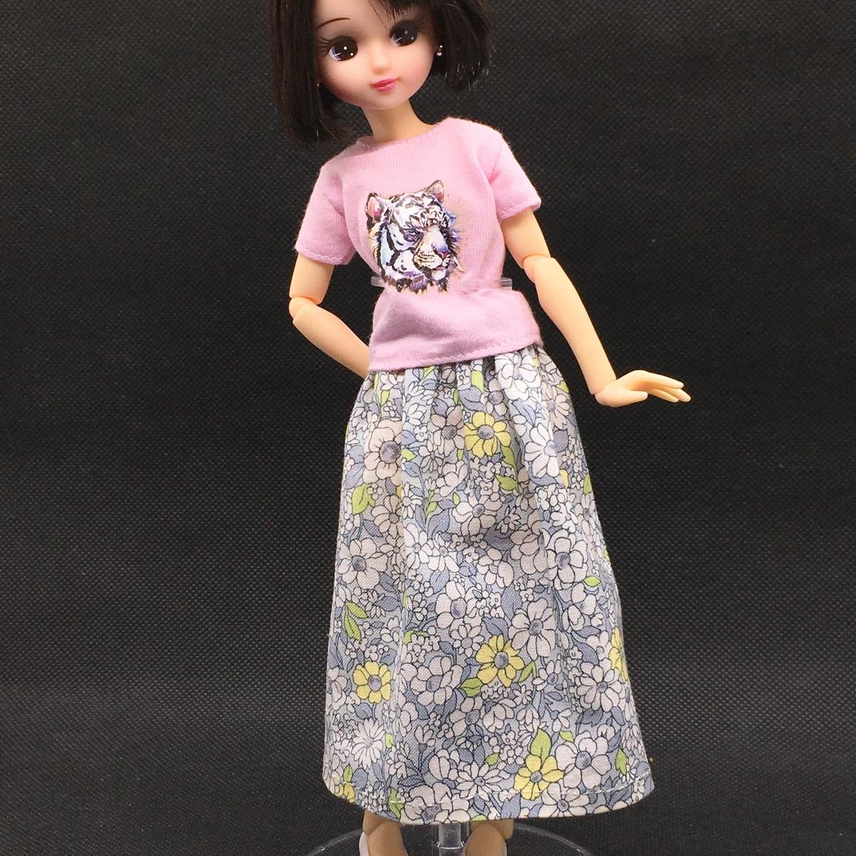 青い花柄の手縫いのロング丈スカートを着たリカちゃん