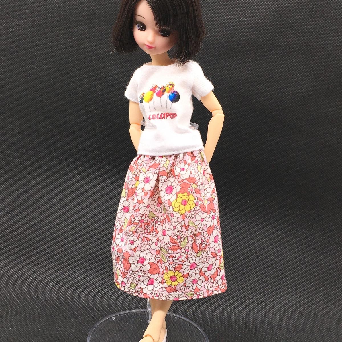 赤い花柄の手縫いのミモレ丈スカートを着たリカちゃん