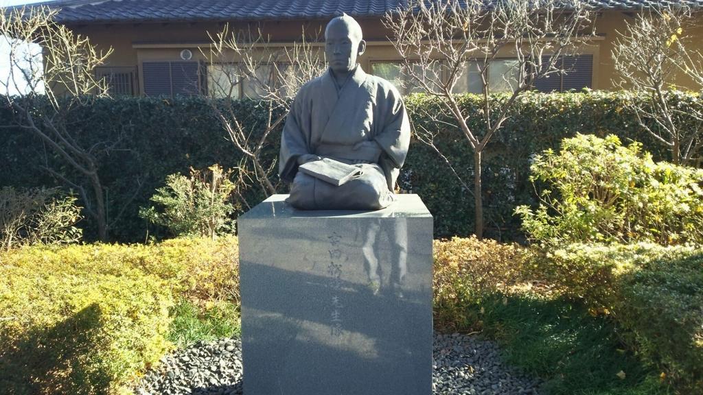 吉田松陰像。正座して手に書物を持っている。