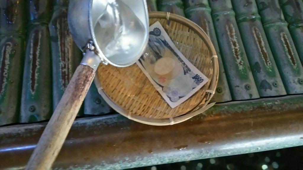 ザルの上に置いた千円札に水をかけて洗っている光景