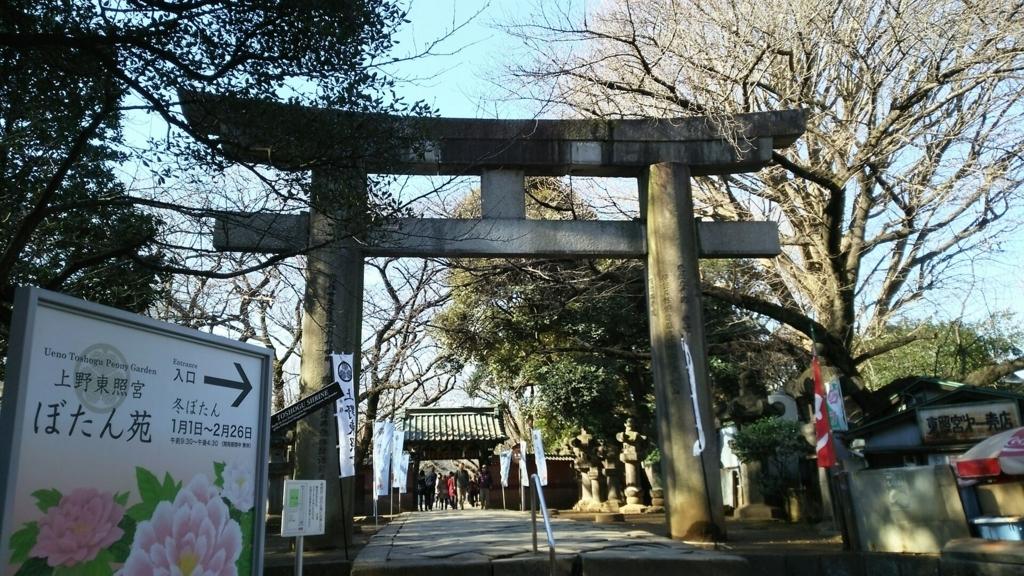 上野東照宮の大石鳥居。鳥居の奥に水舎門が見える。鳥居の右側には寂れた食堂、左側にぼたん苑の看板がある。
