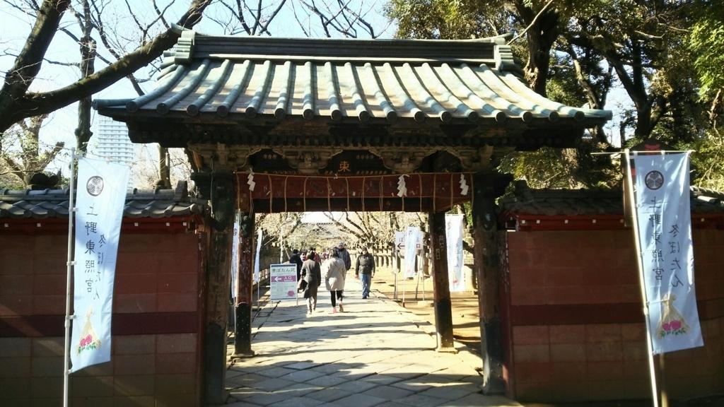 上野東照宮の水舎門。門をくぐって多くの人がお参りに向かっている。門の両脇にぼたん苑ののぼりが立てられている。