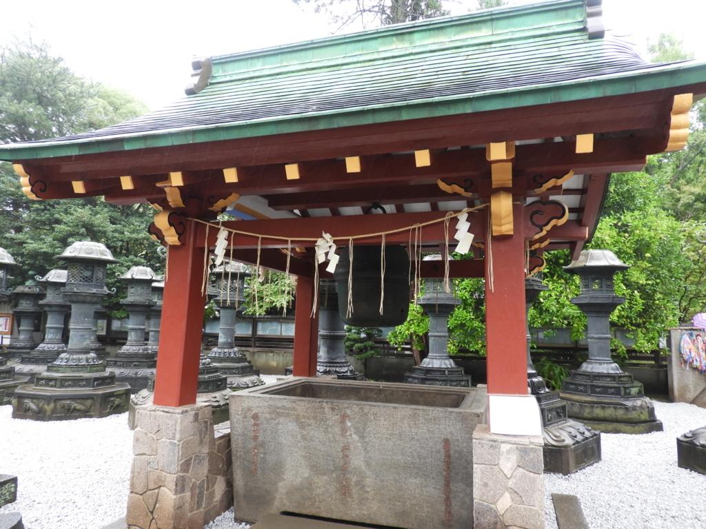 上野東照宮の鈴。赤い柱が見事な水屋の内部に吊るされている。背後に銅灯篭が立っている。