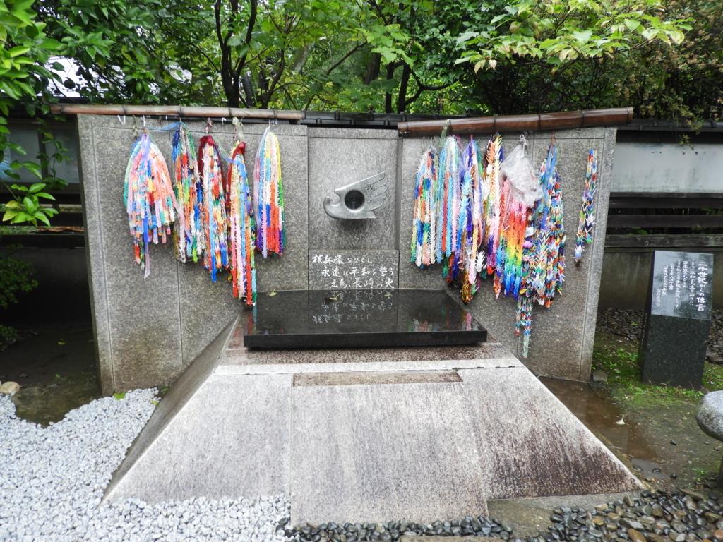「広島・長崎の火」。中央に開けられた窓を通して見ることが出来る。多くの千羽鶴が掛けられている。