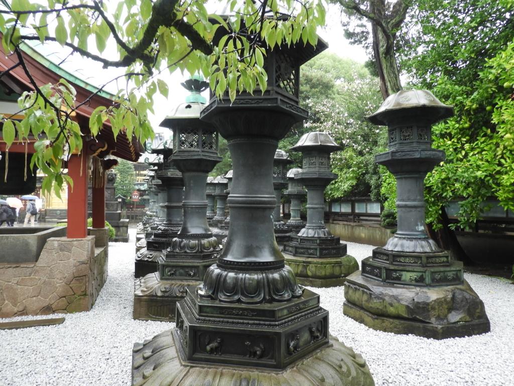 二列に並ぶ銅灯篭。左手に水屋の赤い柱が見える。