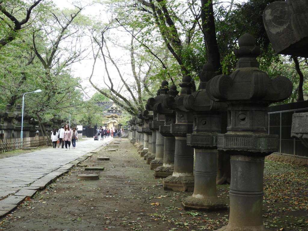 上野東照宮の石灯籠。一直線に伸びた参道の両脇に並んでいる。お参りする人々が石灯籠を見ながら参道を歩いている。