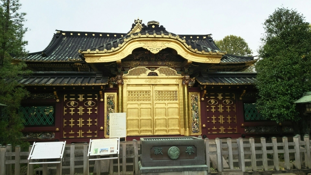 上野東照宮の唐門。金色の門扉の両脇に「昇り龍」「降り龍」の彫刻がある。唐門の両脇には木が植えられ、手前に賽銭箱が置かれている。