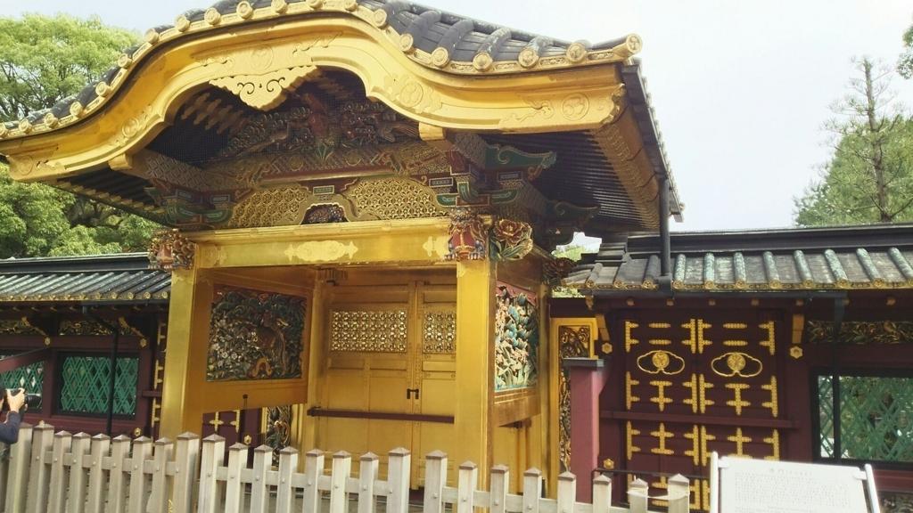 上野東照宮の唐門の内側。金色の門じからえんじ色の塀が伸びている。