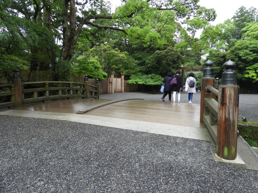 雨に濡れた火除け橋。橋を渡り終わったばかりの3人の女性の奥に一の鳥居が見える