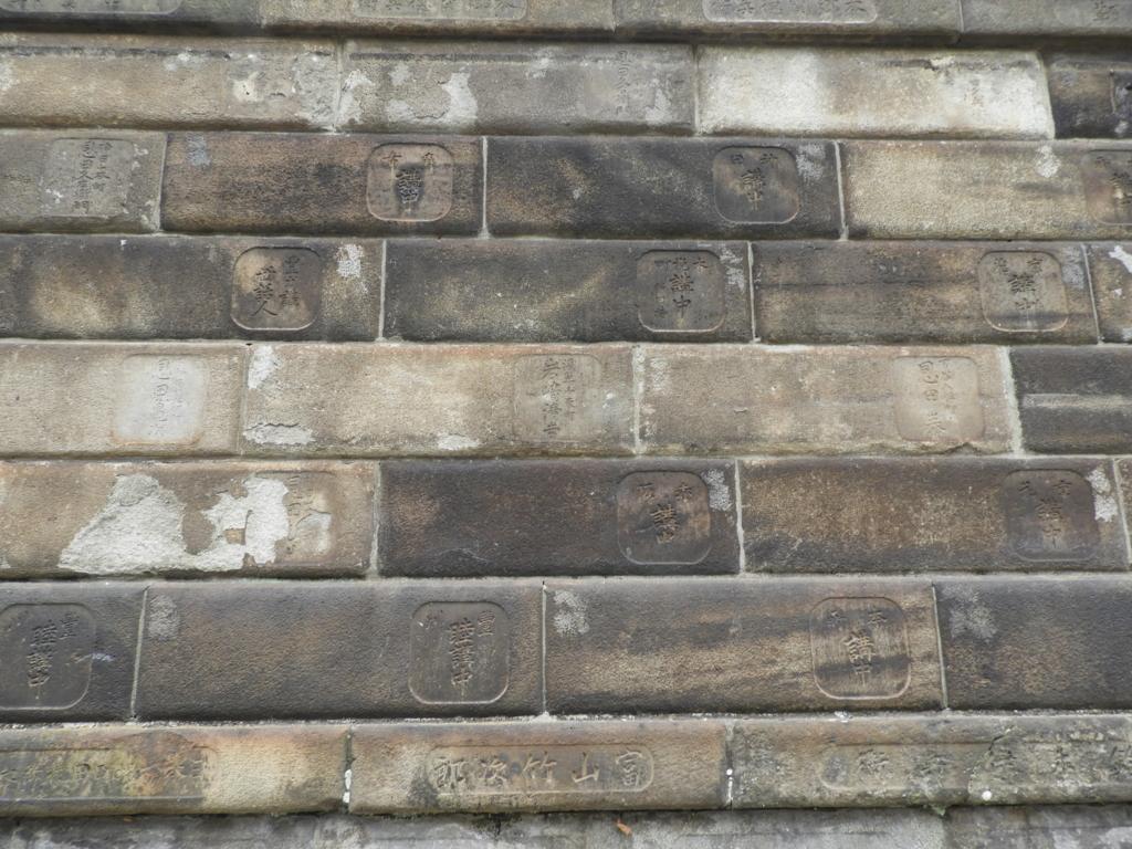 豊川稲荷東京別院の境内を囲む寄進者の名前が刻まれた石垣